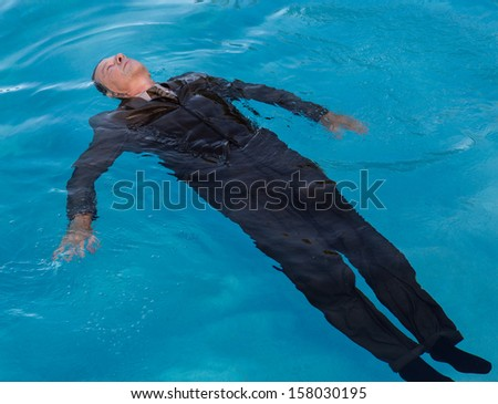 Senior caucasian businessman in suit sinking underwater in deep blue pool looking like drowning as a result of problems - stock photo