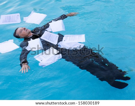 Senior caucasian businessman in suit sinking underwater in deep blue pool worried about being underwater with mortgage payments - stock photo