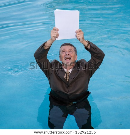 Senior caucasian businessman in suit up to waist in deep blue water worried about drowning in paperwork and holding blank document - stock photo