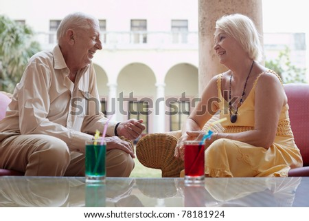 senior caucasian couple sitting in bar at hotel with cocktails and talking. Horizontal shape, side view - stock photo