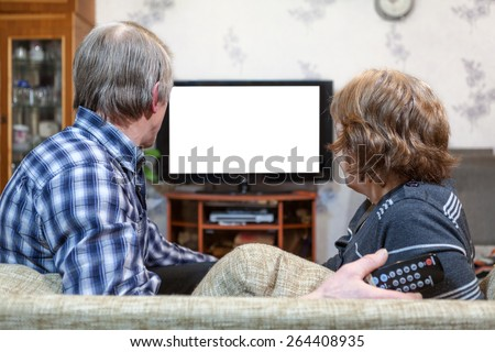 Senior Caucasian couple sitting in front of TV and watching isolated white screen - stock photo