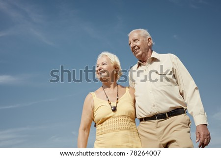 senior caucasian couple walking on sunny day and hugging. Horizontal shape, low angle view, copy space - stock photo