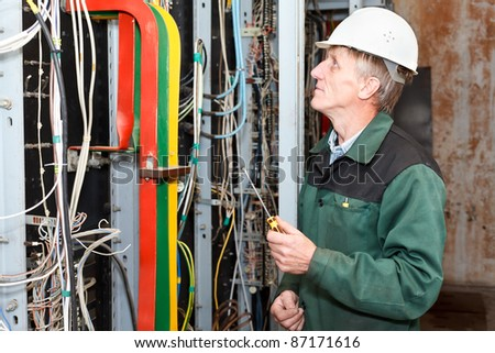 Senior Caucasian electrician working in hardhat with screwdriver, high voltage wires - stock photo
