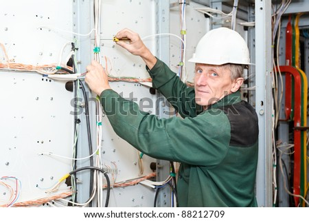 Senior Caucasian electrician working in white hard hat with cables and wires. Screwdriver in hand, looking at camera - stock photo