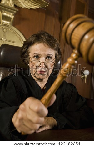 Senior Caucasian judge sitting with mallet in courtroom - stock photo