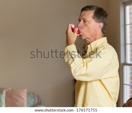 Senior caucasian man at home with asthma inhaler to handle problems with breathing - stock photo