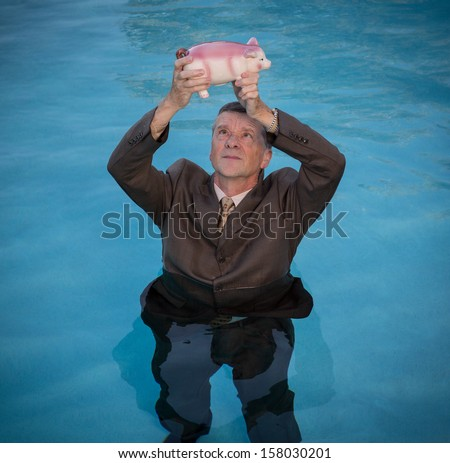 Senior caucasian man holding piggy bank above water as he slowly drowns in debt wearing business suit - stock photo