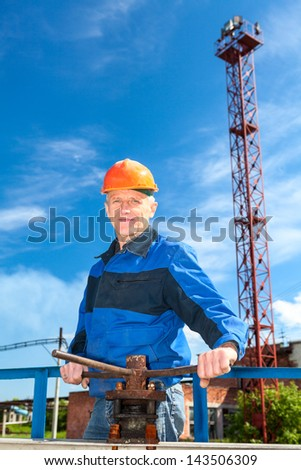 Senior Caucasian man in a working uniform with pipe valve. Looking at camera