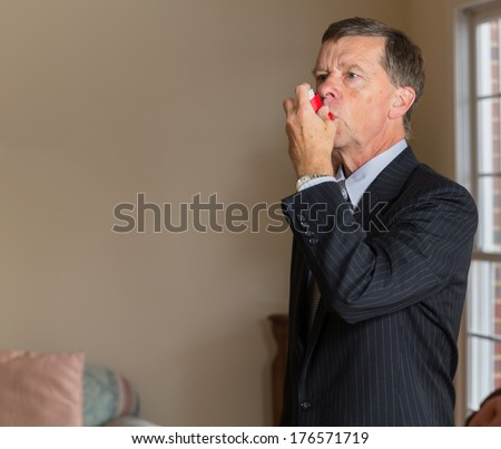 Senior caucasian man  in suit at home with asthma inhaler to handle problems with breathing - stock photo