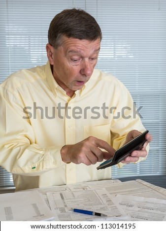 Senior caucasian man preparing tax form 1040 for tax year 2012  showing shock at amount of tax owed - stock photo