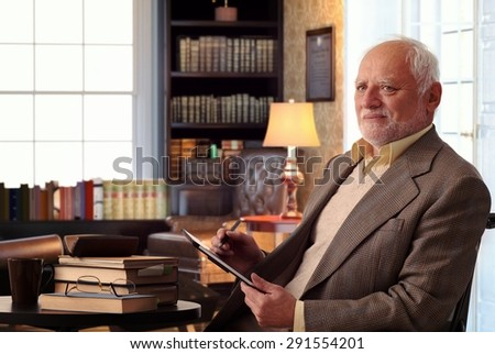 Senior caucasian man sitting in chair, wearing suit at home library, books on table, tablet computer in hand. - stock photo