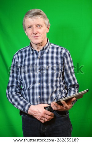 Senior Caucasian man standing with tablet pc in hands, green background - stock photo