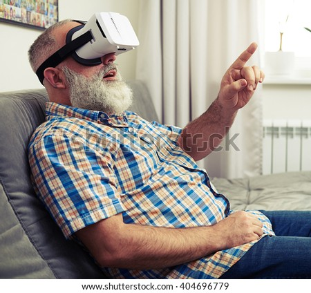 Senior Caucasian man touch something with his finger using VR headset glasses