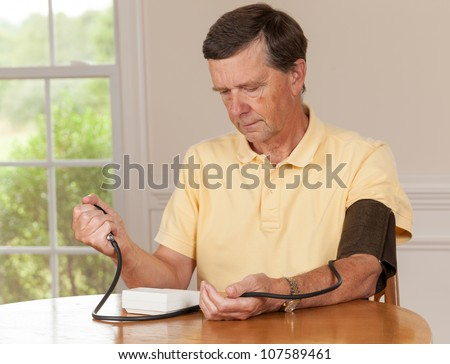 Senior caucasian retired male taking blood pressure at home - stock photo