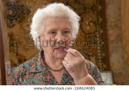 Senior caucasian woman about ninety years old applies lipstick before a three sided mirror in her bed room - stock photo