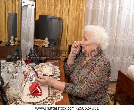 Senior caucasian woman about ninety years old puts on face powder before the mirror in her bed room - stock photo