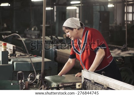Senior caucasian woman in red smock working on the machine at factory sideview