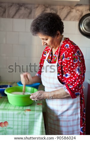 Senior caucasian woman in the kitchen stirring the dough for cakes in a bowl