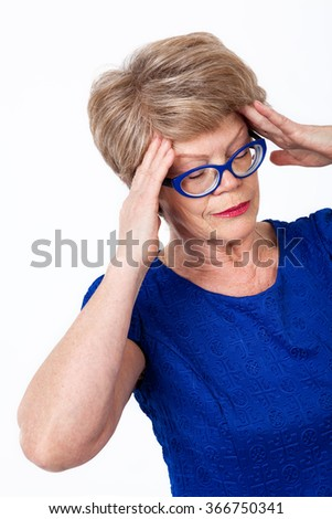 Senior Caucasian woman with headache, holding her head with hands, white background - stock photo