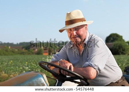 Senior, cheerful gardener on his tractor - stock photo