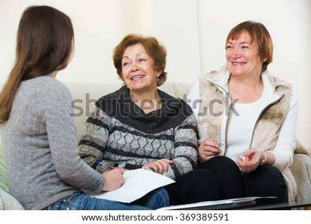 Senior cheerful women consulting with banking agent and smiling at home. Focus on central person  - stock photo