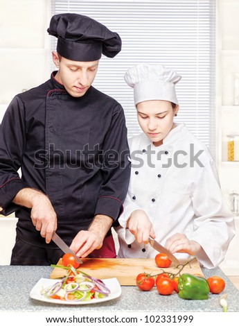 Senior chef teaches young chef to properly cut vegetables - stock photo