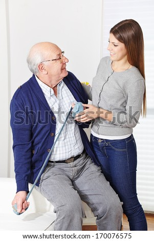 Senior citizen at physiotherapy with woman in a retirement home
