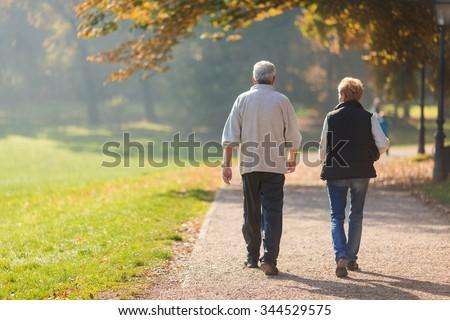 Senior citizen couple taking a walk in a park during autumn morning.  - stock photo