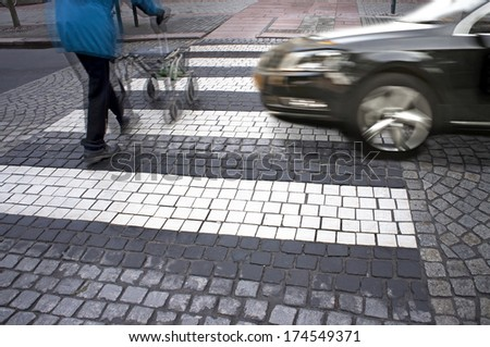 Senior citizen crossing street with fast car approaching  - stock photo