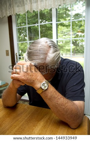 Senior citizen feeling depressed and burdened with hands to his head in a prayerful way - stock photo