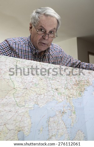 Senior citizen holding a map of europe looking at camera - stock photo