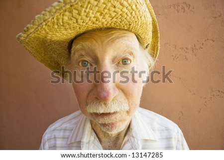 Senior Citizen Man with a Funny Expression Wearing a Straw Cowboy Hat - stock photo
