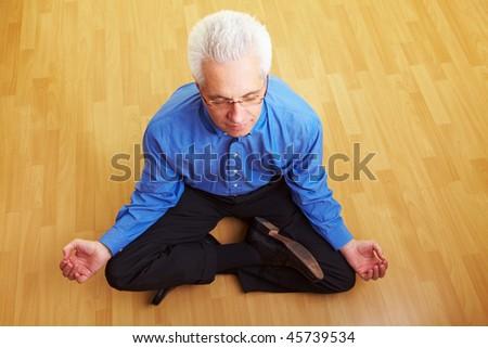 Senior citizen meditating in his living room - stock photo