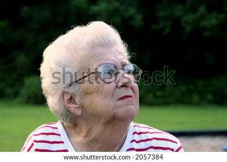 Senior citizen woman at a playground, looking up and away. - stock photo