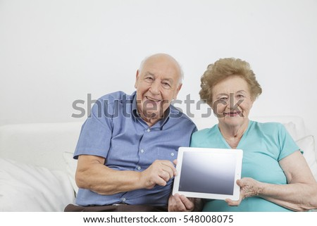 Senior citizen working and playing a mobile tablet computer and using the internet