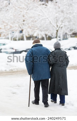 Senior citizens - man with a walking stick and his wife - holding hands and crossing the snow covered street after a heavy snowstorm - stock photo