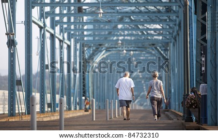 senior citizens walking over bridge - stock photo