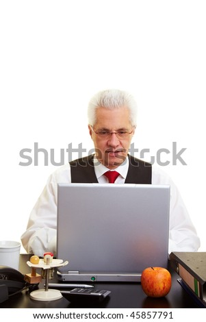 Senior citizent working with a laptop on a desk
