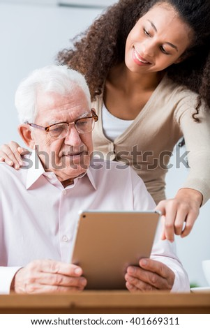 Senior clever man learning how to use new technology. Pretty young caregiver helping man to use tablet