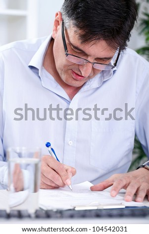 Senior concentrated   business man writing in office - stock photo