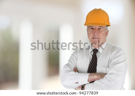 Senior construction worker looking at plans on job - stock photo