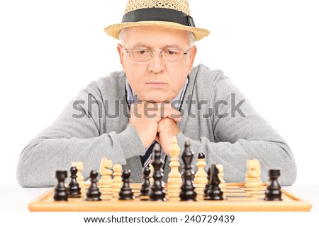 Senior contemplating his next move in game of chess isolated on white background - stock photo