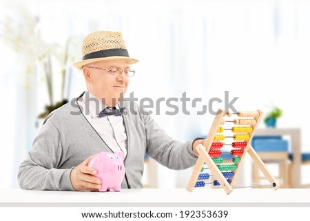Senior counting his savings with abacus indoors - stock photo