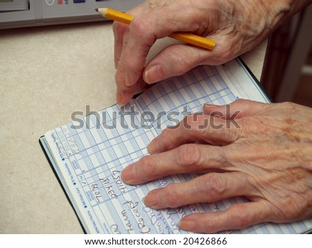 Senior counting money in the checkbook - stock photo