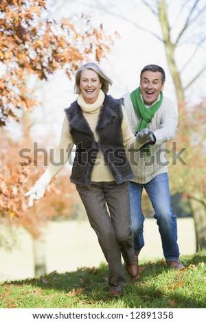 Senior coupl running through autumn woods - stock photo