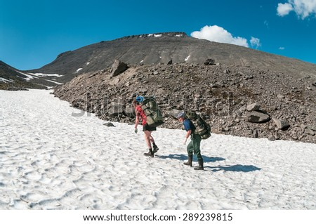 Senior couple a climbers climbing mountain pass together in the snow, side view - stock photo