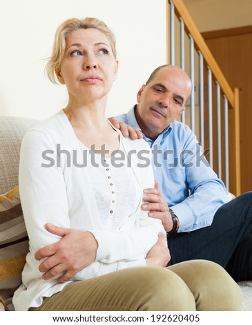 Senior couple after quarrel in room at home