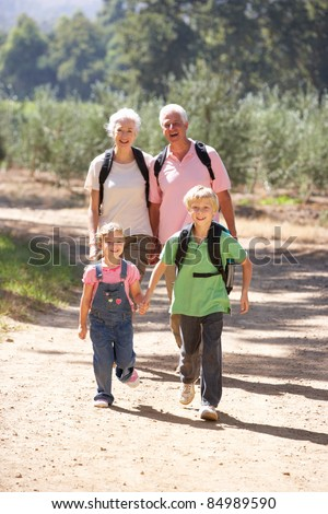Senior couple and grandchildren on country walk - stock photo