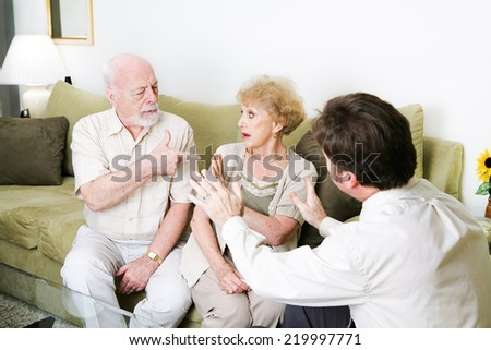 Senior couple arguing in a counseling session.  Copyspace for text.   - stock photo