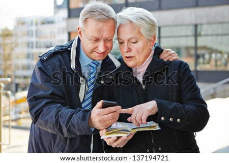 Senior couple as tourists with map and smartphone in a city - stock photo